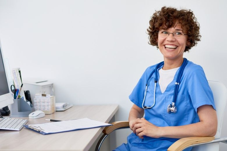 Smiling female nurse in front of desk